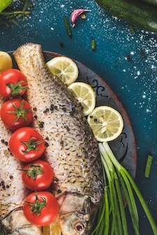 Fish in a decorative platter with lemon, tomato and herbs on a blue table