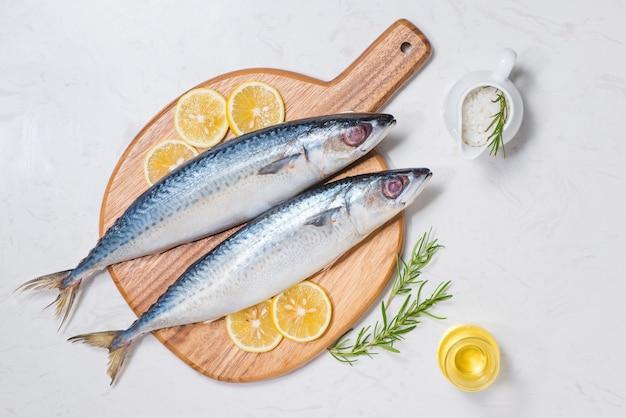 さまざまな食材を使った魚料理。木製のテーブルにレモン スライスとハーブで飾られた新鮮な生の魚。