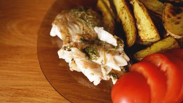 Рыбное блюдо - жареное рыбное филе с жареным картофелем и овощами со специями и розмарином, вид сверху, копия пространства