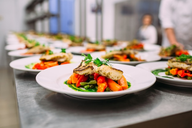 Fish dish with vegetables for catering. lots of plates.