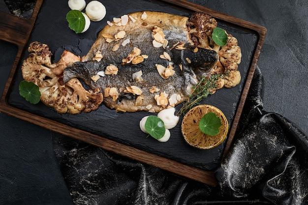 食材を使った暗い素朴な表面に健康的な野菜を添えた魚の形をした裏地のドラドを使った魚料理の調理準備、上面図