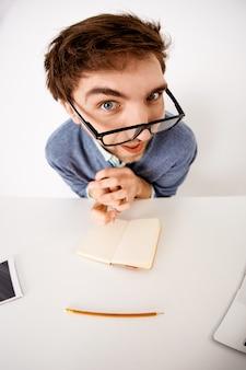 Снимок под большим углом зрения забавного молодого мужчины, сидящего за офисным столом, надевает очки, задумчиво смотрит и интересуется, создает новый контент, записывает идеи в блокнот