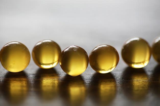 魚の脂肪。病気の治療のための医療製品。タブレットへの健康依存の概念。木製の背景に魚油のカプセル。