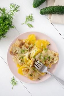 Рыбное филе и картофель с луком на плоском блюде на белом деревянном фоне