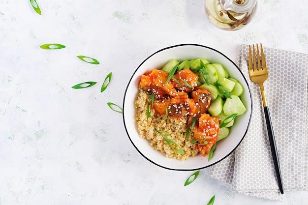 明るい背景のプレートにブルガーとキュウリを添えてトマトソースで調理した魚の切り身。健康的な食事の概念。簡単調理。上面図、フラットレイ、コピースペース