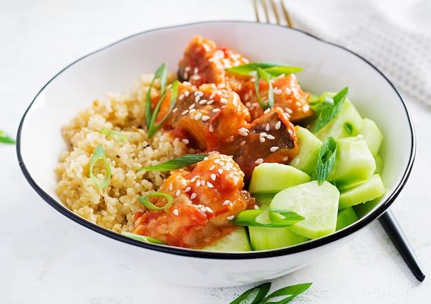 Филе рыбы, приготовленное в томатном соусе с булгуром и огурцом на тарелке на светлой поверхности. концепция здорового питания. легкое приготовление.