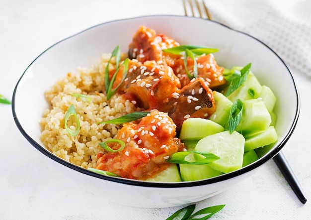 Fish fillet cooked in tomato sauce with bulgur and cucumber on a plate on a light surface. healthy eating concept. easy cooking.