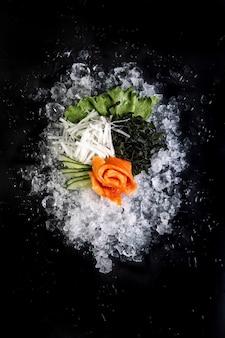 Филе рыбы нарезанное на льду на черном фоне