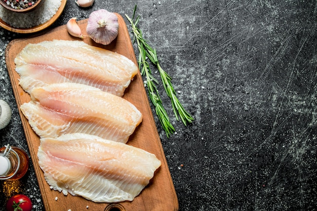 Fish fillet on a cutting board with rosemary, garlic and spices in a bowl. on black rustic