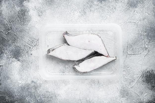 Набор замороженных рыбных филе на столе из серого камня