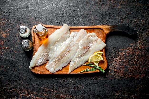 暗い素朴なテーブルにレモン、オイル、スパイスのスライスとまな板の魚の切り身