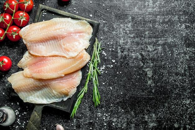 まな板にトマト、ローズマリー、塩を添えた魚の切り身。
