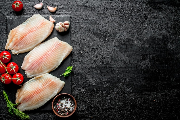 ボウルにディル、トマト、スパイスを入れた黒い石のボード上の魚の切り身。黒の素朴な背景に