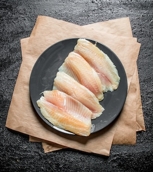 Fish fillet on plate with paper on black rustic table