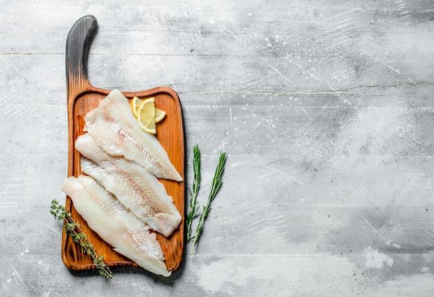 白い素朴なテーブルにレモンスライス、タイム、ローズマリーと魚の切り身