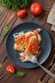 Рыбное филе с помидорами и нарезанным укропом на черной тарелке на деревянном столе