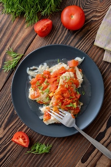 Fish fillet with tomatoes and chopped dill on black plate on wooden table top view