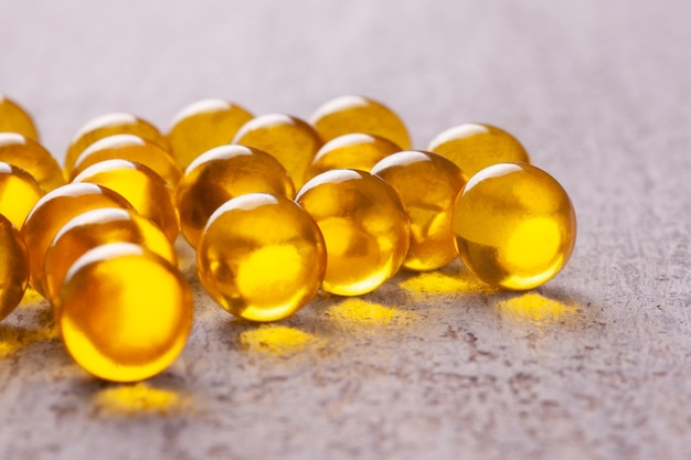 Fish or flaxseed oil in capsules or tablets, vitamins, omega on a wooden table.