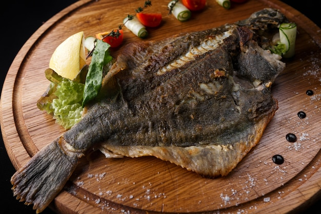 Fish flounder with lemon and vegetables