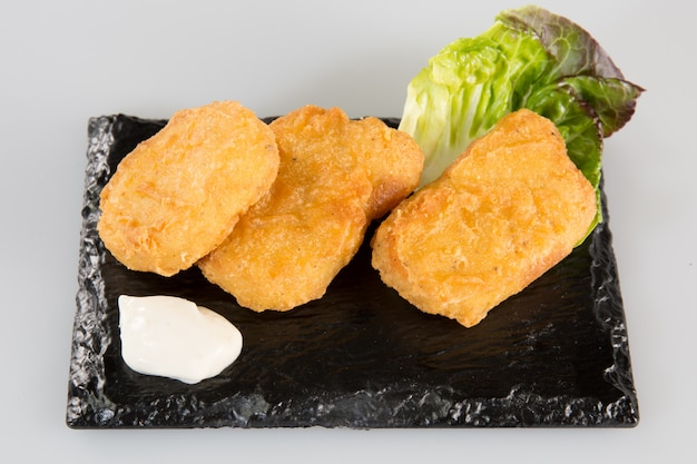Fish fried on a black slate with salad