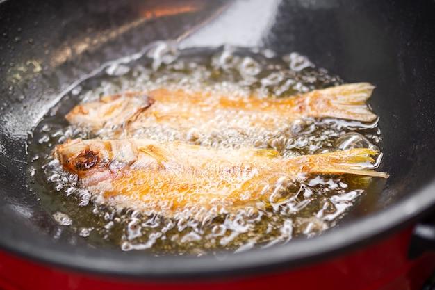 鍋に油を入れて魚を炒める。健康概念のための食品。