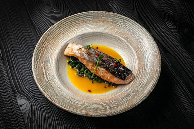 暗い木製のテーブルの上の皿で魚のグリル