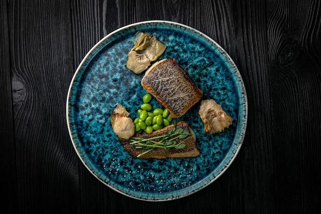 Рыба-гриль на тарелке на темном деревянном столе
