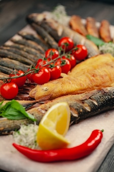 Fish grilled on a plate with vegetables and lemon