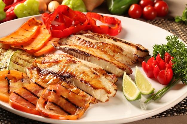 Рыба на гриле с овощами в тарелке.