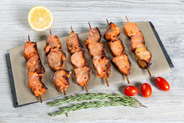 Fish kebabs served on wooden table