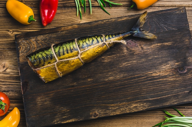 Fish mackerel smoked on a board with tomatoes and pepper