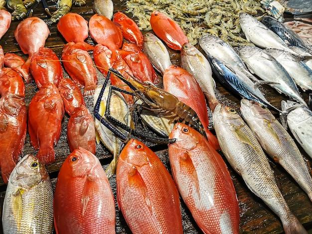 魚市場の概念。木製のテーブルの極端なクローズアップの魚、エビ、エビ、アカザエビ。