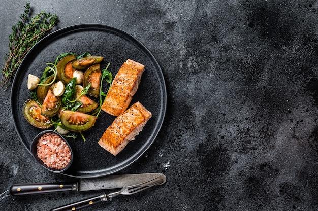 ローストサーモンフィレステーキとルッコラトマトサラダを添えた魚粉。黒の背景。上面図。スペースをコピーします。