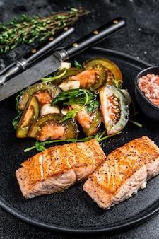 구운 연어 등심 스테이크와 arugula 토마토 샐러드 접시에 생선 식사. 검정색 배경. 평면도.