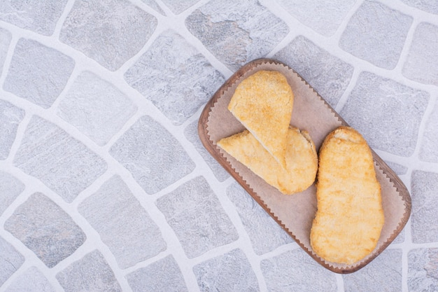 Fish nuggets isolated on a wooden board.