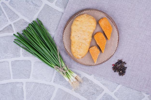 Pepite di pesce su un piatto di legno con cipolle verdi.