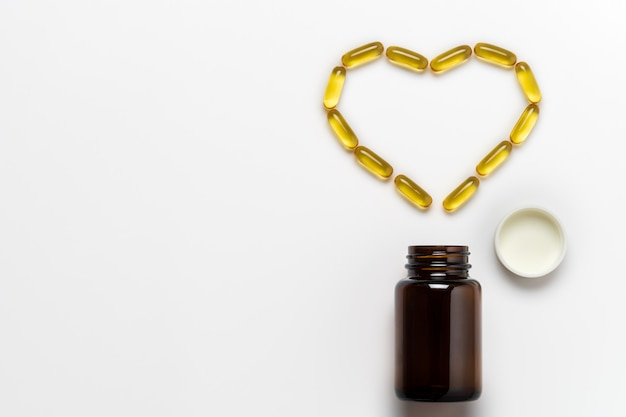 Fish oil capsule is arranged into the heart shape on white background.