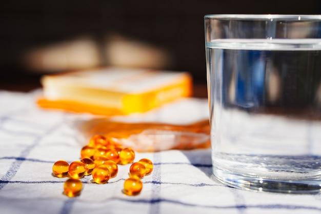 魚油カプセルとテーブルの上のコップタラ肝油オメガ栄養補助食品スポーツ..。