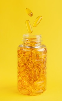 Fish oil capsules falling into the bottle on yellow wall.