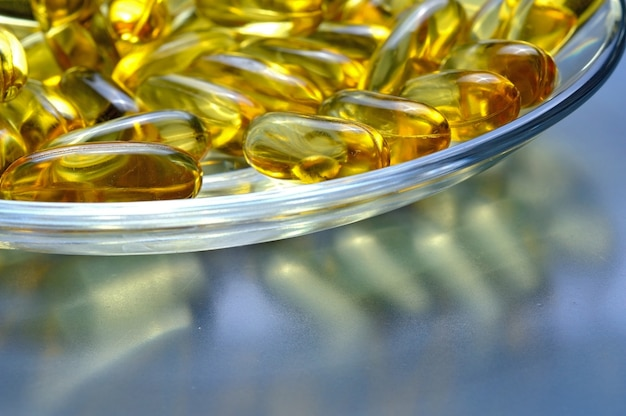 Fish oil capsules on a glass plate. a lot of vitamin omega 3. close-up.