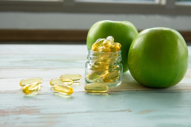 Fish oil capsules and green apple on wooden table, healthcare concept