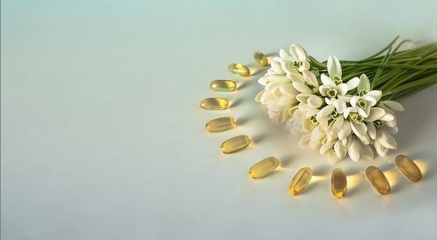 Капсулы рыбьего жира на белой поверхности с букетом весенних цветов.
