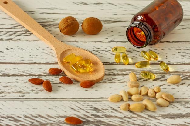 Капсулы рыбьего жира на деревянных фоне и текстуре, витамин d, добавка омега, выборочный фокус.