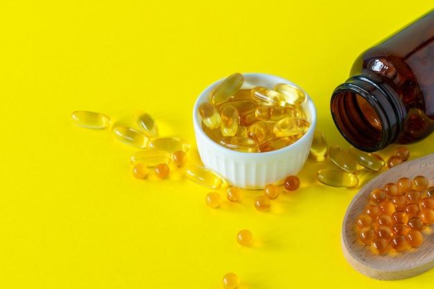 Капсулы рыбьего жира на желтом фоне, витамин d, добавка омега, селективный фокус.