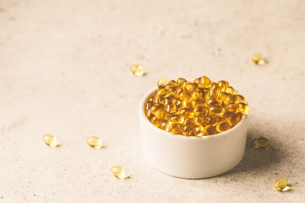 Fish oil capsules in white bowl on gray background