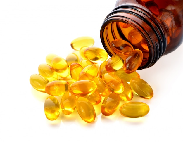 Fish oil capsules with omega 3 and vitamin d in a glass bottle