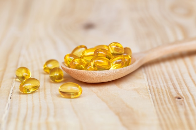 Fish oil capsules with omega 3 and vitamin d on spoon wood