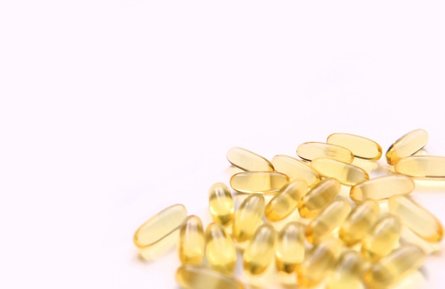 Fish oil capsules with omega 3 and vitamin d on a white background