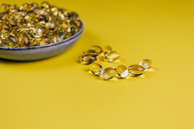 Fish oil in capsules on yellow