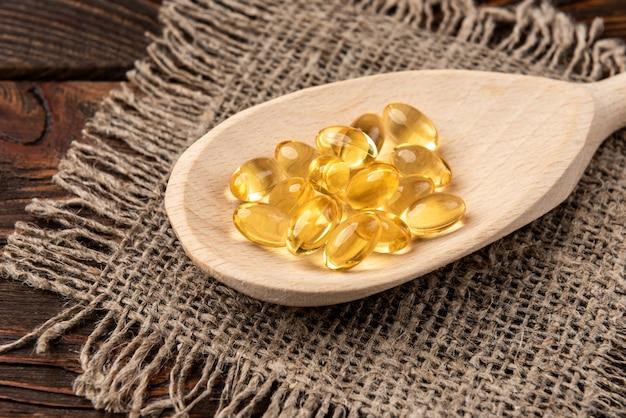 Fish oil on dark wooden table.